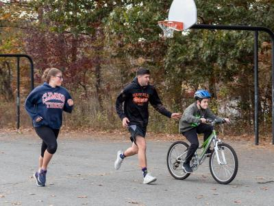 student rides bike with instructors
